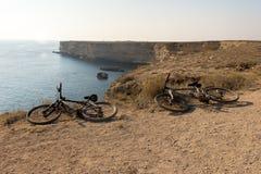 Two bikes on the sea coast. Two bikes lying on the ground on the sea coast Royalty Free Stock Image