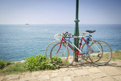Two bikes tied to pole. Two bicycles tied to a street pole with a view of the open sea in Rovinj, Croatia. Rovinj is a popular tourist destination on the Royalty Free Stock Photos