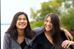 Two smiling biracial teen girls smiling outdoors by lake, huggi stock photography