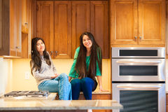 Two biracial teen girls sitting on kitchen counter smiling toget Royalty Free Stock Photos