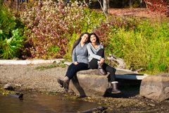 Two teen girls sitting on rock along lake in autumn Royalty Free Stock Photo