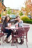 Two teen girls at outdoor cafe drinking boba tea together Stock Photo