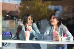 Two teen girls at outdoor cafe drinking boba tea together Stock Photography