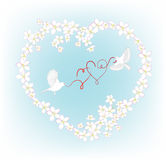 Two birds fly and carry in its beak decorative hearts Royalty Free Stock Photos