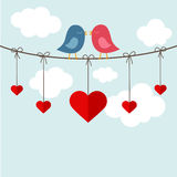 Two birds kissing on a cable. Two birds in love on a cable with hanging hearts Royalty Free Stock Photography