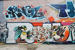 Two birds painted on a brick wall. Stock Image