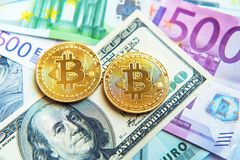Two bitcoins on dollar and euro bills Investment, exchange rate, wealth, luxury, success, stock exchange - concept.  royalty free stock image
