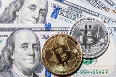 Two Bitcoins on hundred dollars bills. Closeup, macro shot Royalty Free Stock Photography