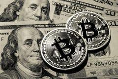 Two Bitcoins on hundred dollars bills. Closeup, macro shot Royalty Free Stock Photos
