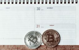 Two bitcoins  are lie on the planing. On the calendar are the last days of December 2017. The concept of crypto currencies Royalty Free Stock Image