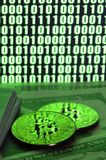 Two bitcoins lies on a pile of dollar bills on the background of a monitor depicting a binary code of bright green zeros and one u. Nits on a black background stock photo