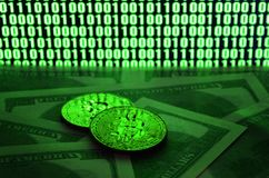 Two bitcoins lies on a pile of dollar bills on the background of a monitor depicting a binary code of bright green zeros and one u Royalty Free Stock Photo