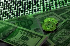 Two bitcoins lies on a pile of dollar bills on the background of a monitor depicting a binary code of bright green zeros and one u. Nits on a black background royalty free stock photo