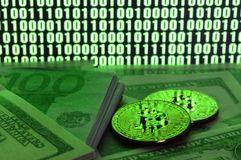 Two bitcoins lies on a pile of dollar bills on the background of a monitor depicting a binary code of bright green zeros and one u. Nits on a black background royalty free stock photos