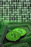 Two bitcoins lies on a pile of dollar bills on the background of a monitor depicting a binary code of bright green zeros and one u. Nits on a black background royalty free stock photography