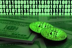 Two bitcoins lies on a pile of dollar bills on the background of a monitor depicting a binary code of bright green zeros and one u. Nits on a black background stock image
