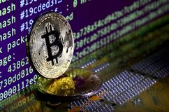 Two bitcoins lies on a videocard surface with background of screen display of cryptocurrency mining by using the GPUs Stock Images
