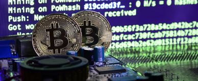 Two bitcoins lies on a videocard surface with background of screen display of cryptocurrency mining by using the GPUs Stock Image