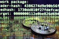 Two bitcoins lies on a videocard surface with background of screen display of cryptocurrency mining by using the GPUs Royalty Free Stock Photography