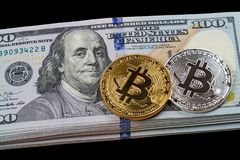 Two bitcoins on a pile of dollars royalty free stock images