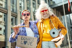 Two bizarre elderly hippies performing in the street. Bizarre hippies. Two bizarre elderly hippies feeling unbelievably amazing while performing in the street royalty free stock images