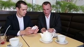 Two biznessmen pay transaction through online banking. Two businessmen sitting in a cafe and pay transactions through Internet Banking stock video