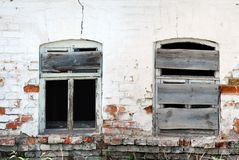 Two Bkoken Windows. Two Cracked Broken Windows on Damaged Brick Wall in Abandoned House Building Stock Photography