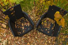 Two black armchairs in the garden. In the gazebo. Fallen yellow autumn leaves Royalty Free Stock Photos