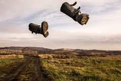Two black boots fly across the sky in the middle of an autumn field royalty free stock image
