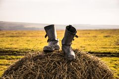 Two black boots on a haystack on a Sunny day stock image