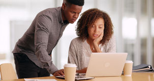 Two black business people working on a laptop while drinking coffee in an office.  Stock Photo