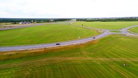 Two black cars quickly go on the high-speed route. Aerial footage. Aerial footage of green fields and high speed road stock footage