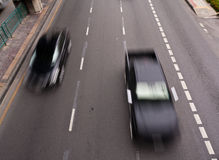 Two black cars running on the road. In motion blur Stock Photo