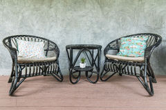 Two black chairs and a coffee table on loft wall background Royalty Free Stock Photos