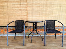 Two black chairs with round table on wood floor, brick wall and. Bamboo curtain Stock Photography