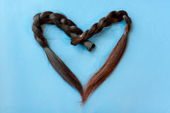 Two  black chopped-off braids of human hair in a heart shape Royalty Free Stock Photos