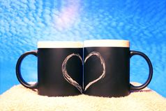 Two black circles with a symbol of love against the blue sky. Heart drawn in white chalk on a black background. Valentine`s Day. royalty free stock photo