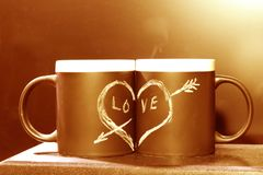 Two black circles with a symbol of love in the dark illuminated by a candle. Heart pierced by an arrow drawn in white chalk on a royalty free stock photo