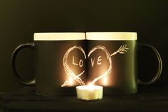 Two black circles with a symbol of love in the dark illuminated by a candle. Heart pierced by an arrow drawn in white chalk on a royalty free stock photography
