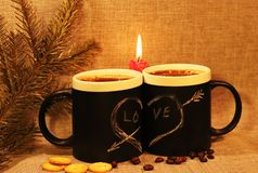 Two black circles with a symbol of love with a red candle and a branch of spruce. Heart pierced by an arrow drawn in white chalk stock photo