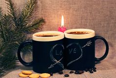 Two black circles with a symbol of love with a red candle and a branch of spruce. Heart pierced by an arrow drawn in white chalk stock photography