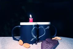Two black circles with a symbol of love with a red candle and sweets. Heart pierced by an arrow drawn in white chalk on a black royalty free stock photo