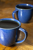 Two Black Coffees in Blue Mugs. Two cups of black coffee in blue marbled mugs Stock Photo