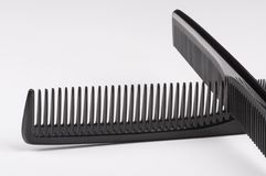 Two black combs against white background, closeup. Crossed two black combs against white background, closeup Stock Photos