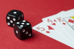 Two black cubes and playing cards royalty free stock photography