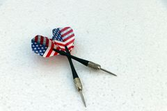Two black dart with USA flag of the wing on the white foam board stock images