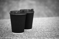 Two black disposable cups of coffee with lids are standing on the stone parapet stock photos