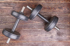 Two black dumbbells, top view. Heavy objects for lifting in gym on wooden background Royalty Free Stock Photos