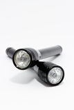 Two black flashlights on white background Stock Photos