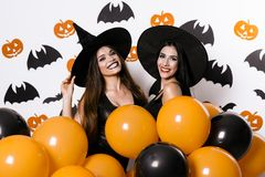 Two black-haired sexy models posing in Halloween costumes holding in their hands ballons Royalty Free Stock Photography